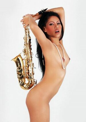 Fully naked oriental babe playing the saxophone